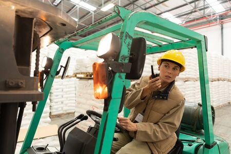 Front view of female worker talking on walkie-talkie while driving forklift in warehouse. This is a freight transportation and distribution warehouse. Industrial and industrial workers concept Reklamní fotografie
