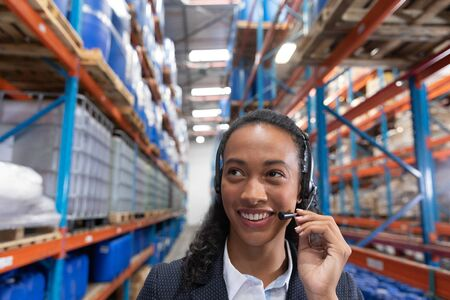 Close-up of female manager talking on headset in warehouse. This is a freight transportation and distribution warehouse. Industrial and industrial workers concept Reklamní fotografie