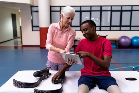 Front view of Caucasian active senior female trainer and disabled African-american man discussing over digital tablet in sports center. Sports Rehab Centre with physiotherapists and patients working together towards healing Archivio Fotografico - 128270911