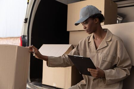 Front view of delivery woman checking parcel near van outside the warehouse. This is a freight transportation and distribution warehouse. Industrial and industrial workers concept