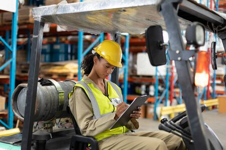 Female staff writing on clipboard while sitting on forklift in warehouse. This is a freight transportation and distribution warehouse. Industrial and industrial workers concept