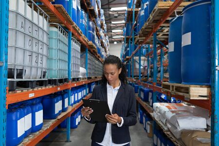 Front view of female manager looking at clipboard in warehouse. This is a freight transportation and distribution warehouse. Industrial and industrial workers concept