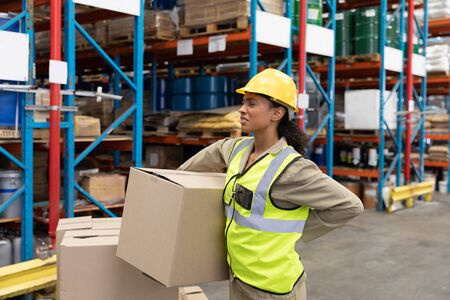 Female staff suffering from back pain while holding heavy cardboard box in warehouse. This is a freight transportation and distribution warehouse. Industrial and industrial workers concept