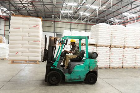 Side view of female worker driving forklift in warehouse. This is a freight transportation and distribution warehouse. Industrial and industrial workers concept