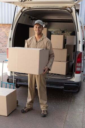 Front view of delivery man carrying cardboard boxes outside the warehouse. This is a freight transportation and distribution warehouse. Industrial and industrial workers concept
