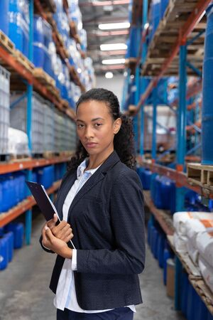Portrait of female manager standing with clipboard in warehouse. This is a freight transportation and distribution warehouse. Industrial and industrial workers concept Banco de Imagens