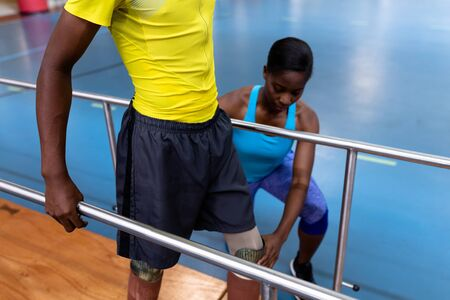 Front view of African-american Female physiotherapist helping disabled man walk with parallel bars in sports center. Sports Rehab Centre with physiotherapists and patients working together towards healing