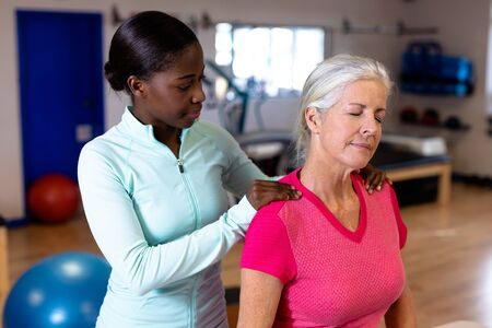 Front view of female physiotherapist giving back massage to active senior woman in sports center. Sports Rehab Centre with physiotherapists and patients working together towards healing Banque d'images