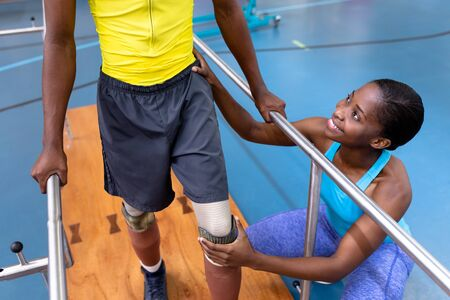 High angle view of African-american physiotherapist assisting disabled African-american man walk with parallel bars in sports center. Sports Rehab Centre with physiotherapists and patients working together towards healing