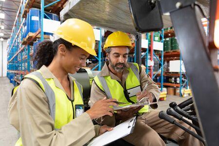 Personnel masculin et féminin multiethnique discutant sur le presse-papiers dans l'entrepôt. Il s'agit d'un entrepôt de transport et de distribution de marchandises. Concept de travailleurs industriels et industriels Banque d'images