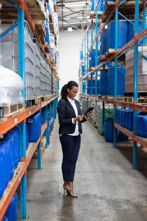 African American female manager using digital tablet in warehouse. This is a freight transportation and distribution warehouse. Industrial and industrial workers concept Stock Photo