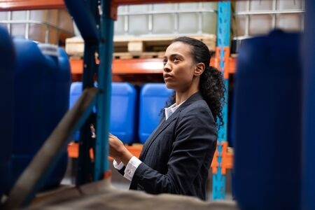 Side view of female manager checking stocks in warehouse. This is a freight transportation and distribution warehouse. Industrial and industrial workers concept