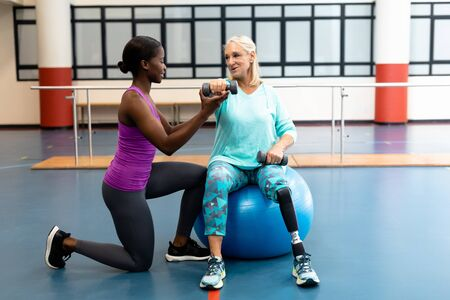 Side view of African-american Female trainer assisting disabled Caucasian senior woman to exercise with dumbbell in sports center. Sports Rehab Centre with physiotherapists and patients working together towards healing Imagens