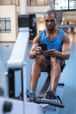 Front view of African-american Fit man using mobile phone while exercising on rowing machine in fitness center. Bright modern gym with fit healthy people working out and training