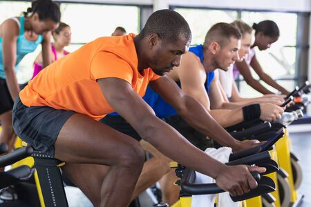Side view of fit people exercising on exercise bike in fitness center. Bright modern gym with fit healthy people working out and training at spin class