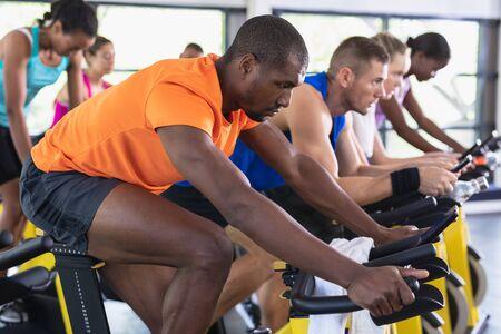 Widok z boku sprawnych osób ćwiczących na rowerze stacjonarnym w centrum fitness. Jasna, nowoczesna siłownia z wysportowanymi, zdrowymi ludźmi ćwiczącymi i trenującymi na zajęciach wirowania