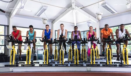 Front view of diverse fit people exercising on exercise bike in fitness center. Bright modern gym with fit healthy people working out and training at spin class Stockfoto