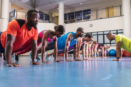 Side view of African-american male trainer training people to perform exercise in fitness center. Bright modern gym with fit healthy people working out and training