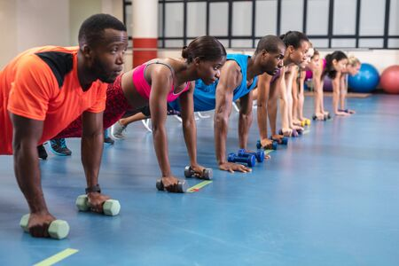 Side view of diverse fit people performing push-up exercise with dumbbells in fitness center. Bright modern gym with fit healthy people working out and training