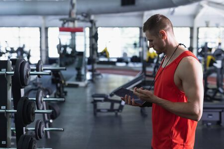 Side view of Caucasian male trainer using digital tablet in fitness center. Bright modern gym with fit healthy people working out and training Stok Fotoğraf