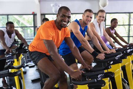 Portrait of diverse fit people exercising on exercise bike in fitness center. Bright modern gym with fit healthy people working out and training at spin class