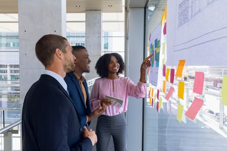 Front view of a young African American businesswoman pointing to charts on a glass wall during a meeting with a young African American and a young Caucasian businessman who are seen in side view. The three of them are standing and smiling in a modern office. Modern corporate start up new business concept with entrepreneur working hard Stock fotó