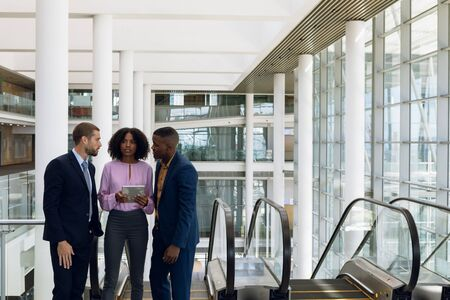 Front view of an African American and a Caucasian businessman standing on an escalator in a modern office with an African American businesswoman holding a tablet computer and talking. Modern corporate start up new business concept with entrepreneur working hard