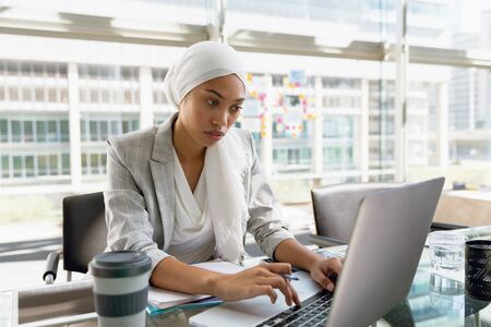 Front view of businesswoman in hijab working on laptop at desk in a modern office. Modern corporate start up new business concept with entrepreneur working hard Stock fotó