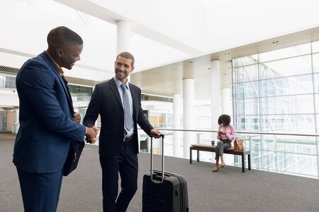 Front view of a young African American and a young Caucasian businessman shaking hands while travelling with luggage. Modern corporate start up new business concept with entrepreneur working hard Stock Photo