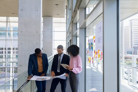 Front view of a young African American businesswoman using tablet computer standing in a meeting with a young African American and a young Caucasian businessman holding blueprints. They are standing on a mezzanine in a modern office building. Modern corporate start up new business concept with entrepreneur working hard