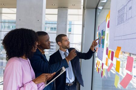 Side view of a young African American businesswoman using tablet computer in a meeting with a young African American and a young Caucasian businessman pointing at charts on a glass wall. The three of them are standing in discussion in a modern office. Modern corporate start up new business concept with entrepreneur working hard