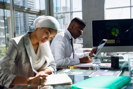Male and females executives working together at desk in office. Modern corporate start up new business concept with entrepreneur working hard