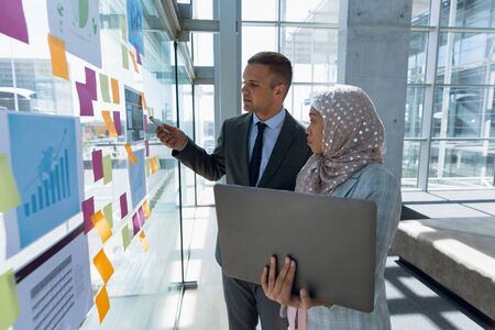 Multi-ethnic Business people discussing over sticky notes in office. Modern corporate start up new business concept with entrepreneur working hard Stock fotó