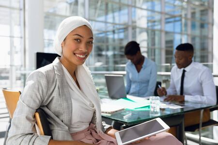 Portrait of Businesswoman in hijab using digital tablet at desk in office. Modern corporate start up new business concept with entrepreneur working hard