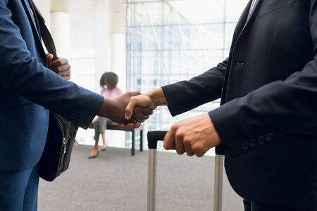 Mid-section of an African American and a Caucasian businessman shaking hands while travelling with luggage. Modern corporate start up new business concept with entrepreneur working hard Stock Photo
