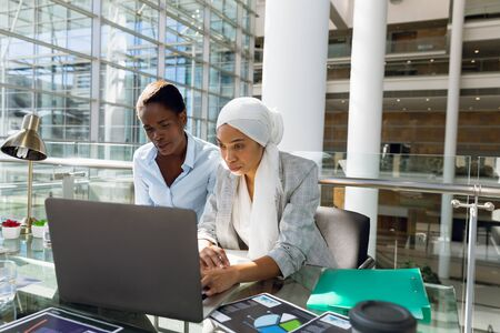 Females executives working together on laptop at desk in office. Modern corporate start up new business concept with entrepreneur working hard