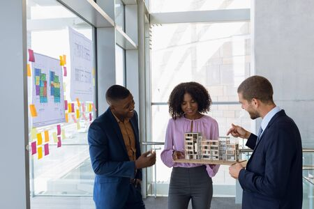 Front view of a young African American female architect with a young African American and a young Caucasian male architect holding an architectural model. The three of them are standing in discussion in a modern office. Modern corporate start up new business concept with entrepreneur working hard Stock fotó