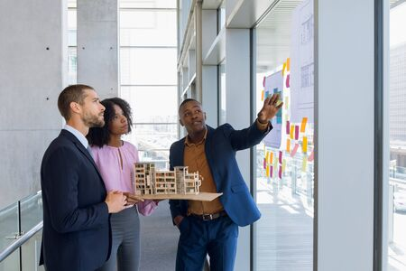 Side view of a young African American businesswoman holding an architectural model standing in a meeting looking at plans with a young African American and a young Caucasian man working together in an architects office. Modern corporate start up new business concept with entrepreneur working hard Stock fotó