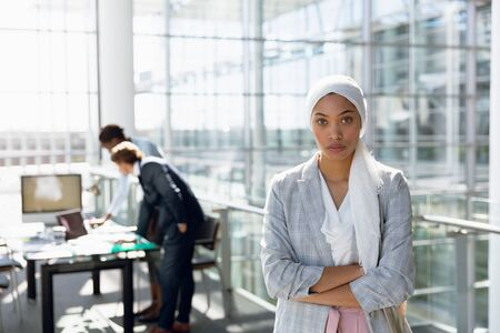 Businesswoman in hijab standing with arms crossed while her colleagues working in background at office. Modern corporate start up new business concept with entrepreneur working hard