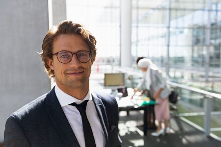 Happy businessman looking at camera while his colleagues working at desk in background at office. Modern corporate start up new business concept with entrepreneur working hard Stock fotó