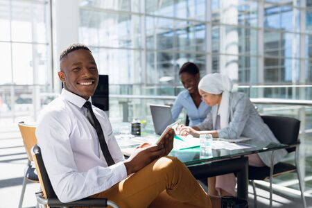 Portrait of happy Businessman using digital tablet at desk in office. Modern corporate start up new business concept with entrepreneur working hard