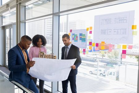 Front view of a young African American female architect holding a model while a young African American and a young Caucasian male architect hold a blue print. The three of them are standing in discussion in a modern office. Modern corporate start up new business concept with entrepreneur working hard Stock fotó
