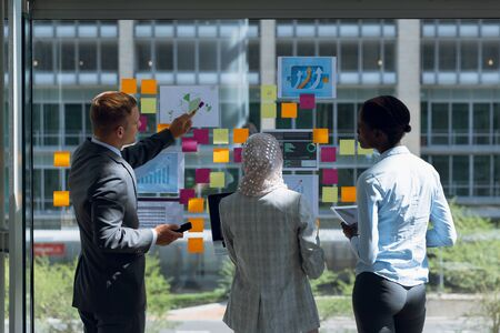 Rear view of Business people discussing over sticky notes in office. Modern corporate start up new business concept with entrepreneur working hard