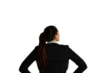 Back view close up of a young mixed race businesswoman with long hair in a ponytail wearing a black jacket, looking up, with her hands on her hips