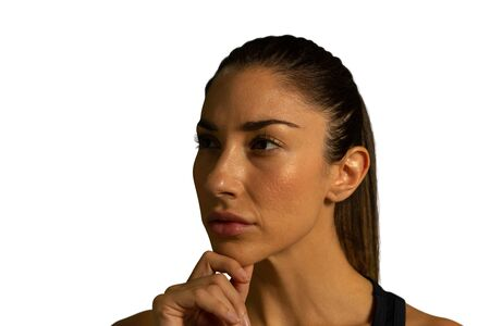 Front view close up of a young mixed race woman looking away in thought, holding her chin
