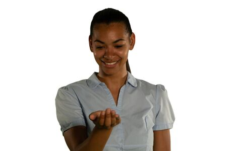 Front view close up of a young mixed race woman with one hand held out and up-turned to hold or receive, looking down, smiling Stockfoto