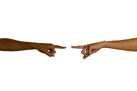 Close up of two arms, of a young Caucasian and a young mixed race woman, with hands reaching out towards each other and fingers extended pointing or touching