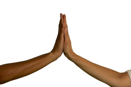 Close up of two raised hands touching each other, palm to palm, one of a young Caucasian and one of a young mixed race woman