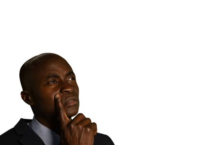 Side view close up of a young African American businessman looking up uncertainly, touching his face with is finger Stockfoto
