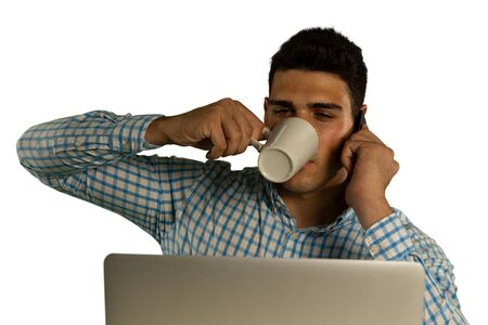 Front view close up of a young mixed race man wearing a checked shirt using a laptop and drinking a cup of coffee while on the phone